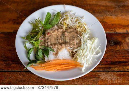 Rice Noodle Eaten With Curry And Fresh Vegetable In A White Plate On A Wooden Table Background. Ferm