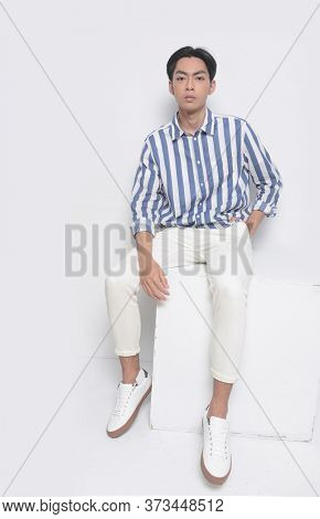 Portrait of handsome man wearing long sleeved new stylish striped shirt with white pants sitting wooden cube