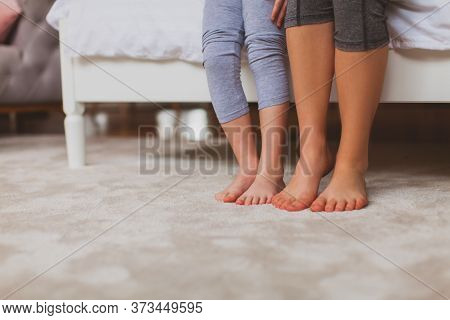 Mother And Daughter Feet On The White Carpet