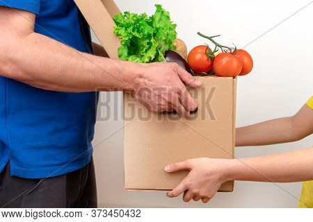 A Delivery Man Hands A Box Of Fresh Vegetables To A Customer On A White Background.