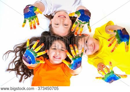 Three Happy And Smiling Children Are Looking At The Camera And Holding Out Their Hands In Paints. Ra