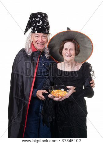 Costumed senior couple handing out Halloween candy