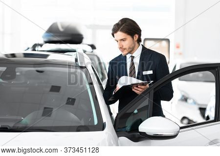 Vehicle Dealership. Car Salesperson With Clipboard Checking Auto Specifications In Local Dealership