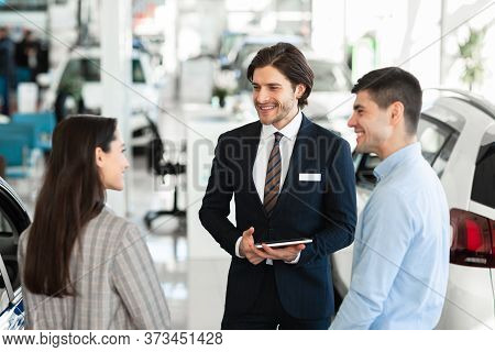Car Sale. Handsome Salesperson With Digital Tablet Talking To Young Family, Showing Vehicles