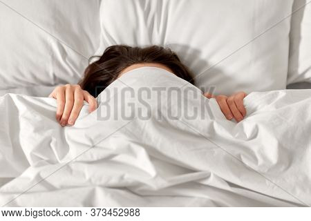 people, bedtime and rest concept - woman lying in bed under white blanket or duvet