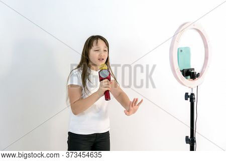 A Teenage Girl With A Microphone In Her Hand Sings And Shoots A Video. Selfies. The Phone Is Mounted