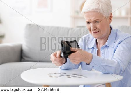Poverty After Retirement. Desperate Senior Woman Shaking Out Last Coins From Wallet At Home, Sufferi
