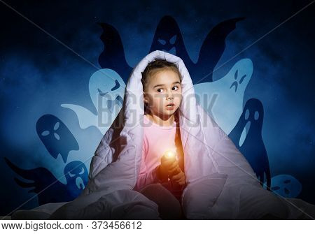 Scared Girl With Flashlight Hiding Under Blanket From Imaginary Phantoms. Frightened Kid Sitting In