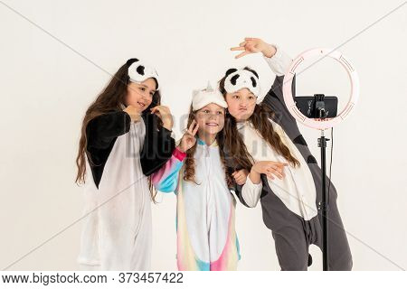 Cute Teenage Girls In Kigurumi And Sleep Masks Smiling And Shoots A Video. Selfies. The Phone Is Mou