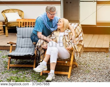 Senior Married Couple Relaxing On Lounge Chairs Near Their Trailer At Campground