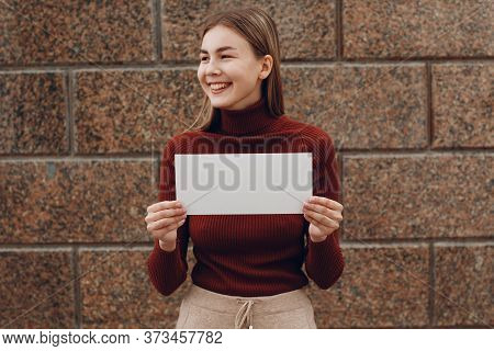 Young Woman Smiling With Smile Holds White Paper In Hand Stone Background. Girl With White Blank Tem