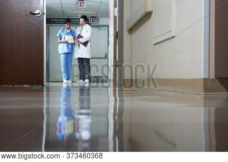 Two doctors looking at document in hospital hallway