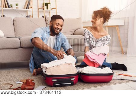 Vacation Concept. Cheerful African Spouses Packing Clothes In Suitcase Sitting On Floor At Home.