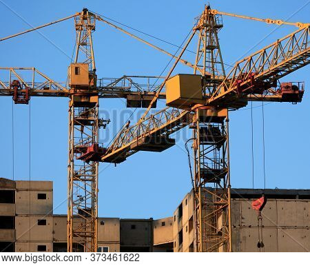 Old Construction Cranes At The Construction Of Panel Apartment Buildings. Construction Site With Cra