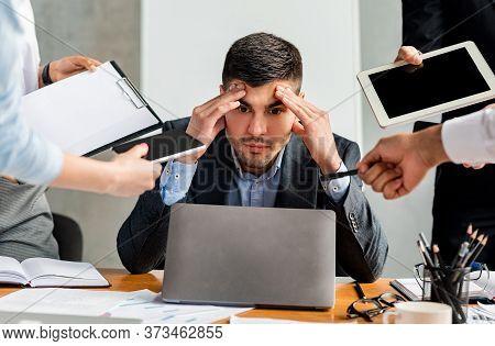 Multitasking. Stressed Businessman At Laptop Touching Head Tired Of Tasks At Work Sitting In Modern