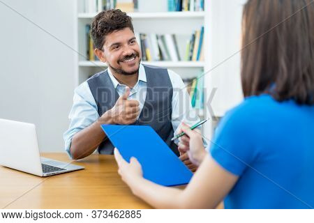 Latin American Businessman And Female Trainee Signing Contractat After Job Interview At Office Of St