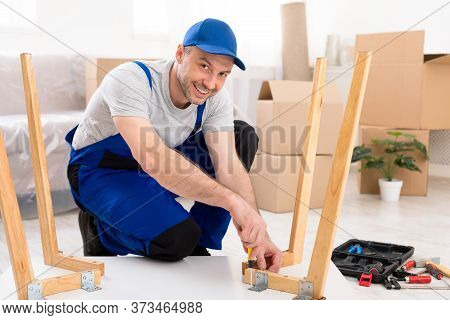 Furniture Transportation And Assembly. Professional Carpenter Assembling Table Sitting On Floor In R