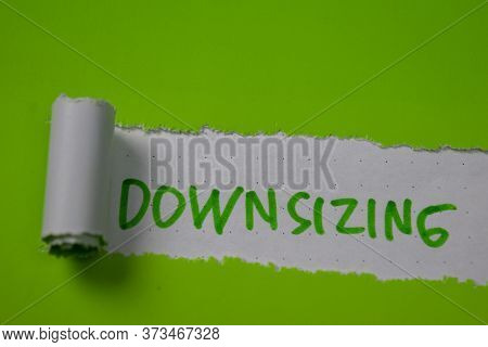 Close Up Downsizing Text Written In Torn Paper