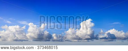 White Fluffy Yet Majestic Cumulus Clouds On Deep Blue Sky Background, Panoramic Format