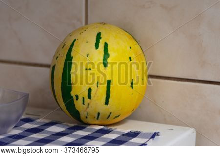 Whole Melon Fruits On A Table On A Blue And White Tablecloth