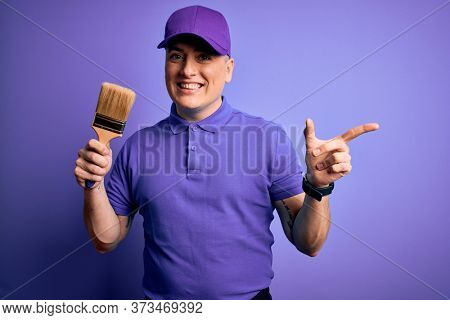 Young modern decorator painter man holding paint brush over purple background very happy pointing with hand and finger to the side