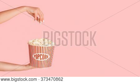Cropped View Of Young Girl Holding Jumbo Bucket Of Popcorn On Pink Background, Free Space. Panorama
