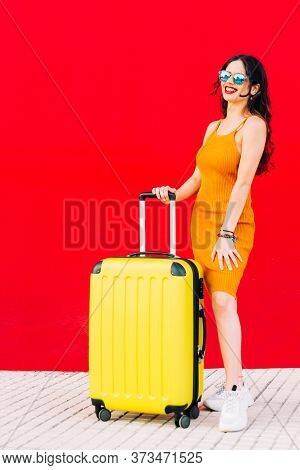 Happy Woman Holding Suitcase And Smiling While Standing