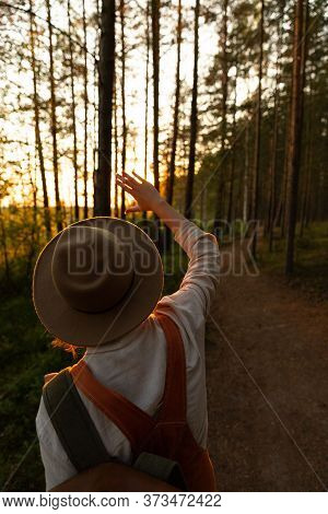 Woman Naturalist In Hat And Orange Overalls With Backpack Looking At The Sun Through Her Fingers At