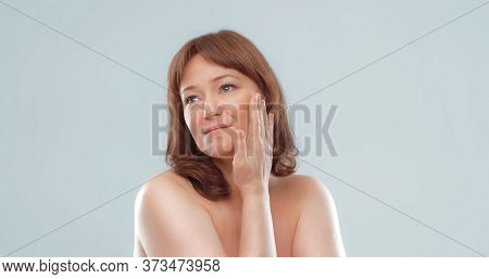 Pretty Mature Female Applies Skin Care Product By Touching Face With Hand. Woman Applying Anti-age C