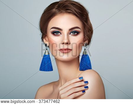 Beautiful Woman With Large Earrings Tassels Jewelry Blue Color. Perfect Makeup And Elegant Hairstyle