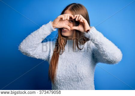 Young beautiful redhead woman wearing casual sweater over isolated blue background Doing heart shape with hand and fingers smiling looking through sign
