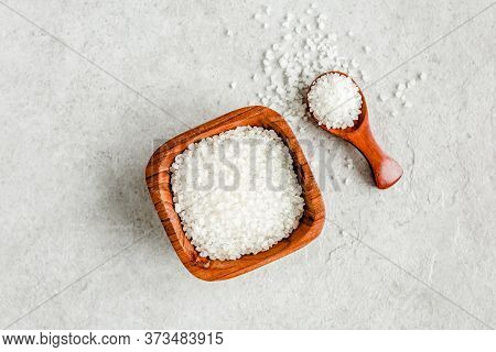 Salt In Wooden Bowl With Scoop On Gray Stone Table. Sea Salt Flat Lay, Top View.