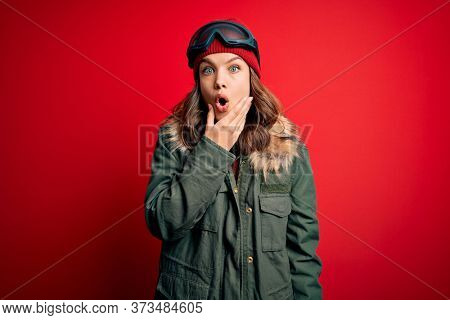Young blonde girl wearing ski glasses and winter coat for ski weather over red background Looking fascinated with disbelief, surprise and amazed expression with hands on chin