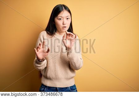 Young beautiful asian woman wearing casual sweater over yellow isolated background Moving away hands palms showing refusal and denial with afraid and disgusting expression. Stop and forbidden.