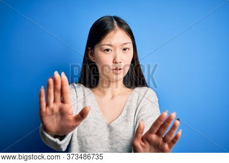 Young beautiful asian woman wearing casual sweater standing over blue isolated background Moving away hands palms showing refusal and denial with afraid and disgusting expression. Stop and forbidden.