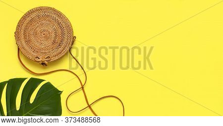 Summer Fashion Flat Lay. Fashionable Handmade Natural Round Rattan Bag And Tropical Palm Leaves On Y