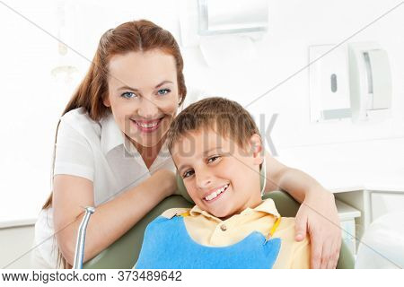 Boy on dental chair at the dentist with dental assistant