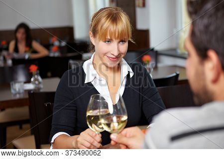 Young couple clinking glasses of wine in the restaurant