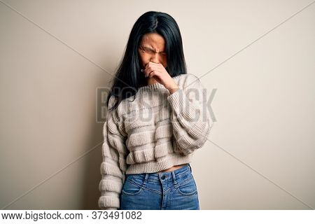 Young beautiful chinese woman wearing casual sweater over isolated white background feeling unwell and coughing as symptom for cold or bronchitis. Health care concept.