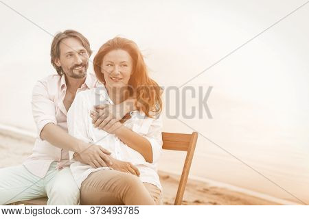Happy Mature Couple Hugs Sitting In Beach Cafe At Sea Side. Portrait Of Hugging Pretty Two People In