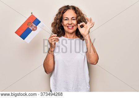 Middle age beautiful patriotic woman holding serbian flag over isolated white background doing ok sign with fingers, smiling friendly gesturing excellent symbol