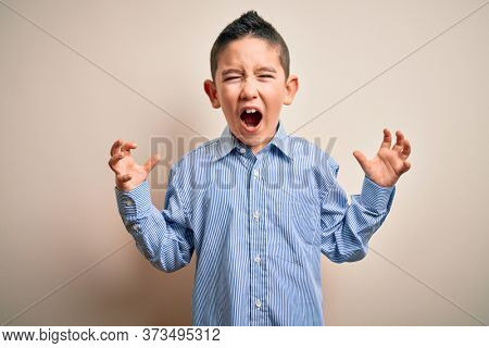 Young little boy kid wearing elegant shirt standing over isolated background crazy and mad shouting and yelling with aggressive expression and arms raised. Frustration concept.