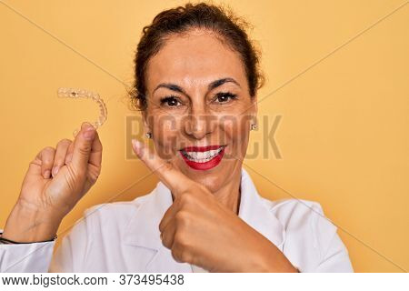 Middle age senior dentist woman holding clear aligner for teeth correction very happy pointing with hand and finger
