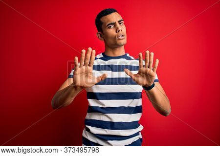 Handsome african american man wearing casual striped t-shirt standing over red background Moving away hands palms showing refusal and denial with afraid and disgusting expression. Stop and forbidden.