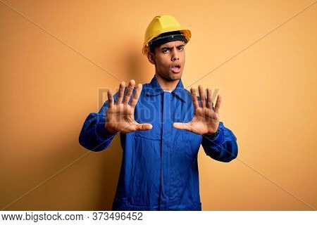 Young handsome african american worker man wearing blue uniform and security helmet Moving away hands palms showing refusal and denial with afraid and disgusting expression. Stop and forbidden.