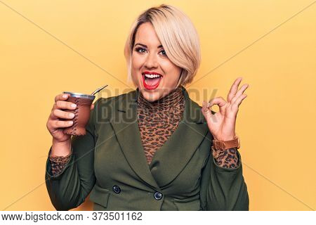 Beautiful blonde plus size woman drinking mate infusion beverage over yellow background doing ok sign with fingers, smiling friendly gesturing excellent symbol