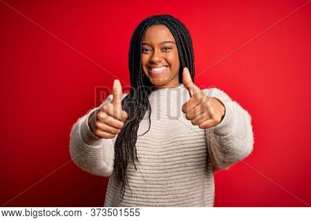 Young african american woman wearing casual winter sweater over red isolated background approving doing positive gesture with hand, thumbs up smiling and happy for success. Winner gesture.