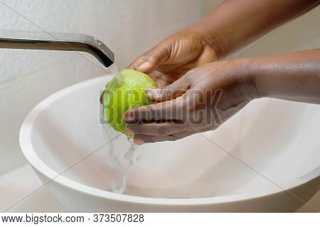 African Female Hands Wash Green Apple Under The Tap. Cook African Woman Washes A Bunch Of Green Appl