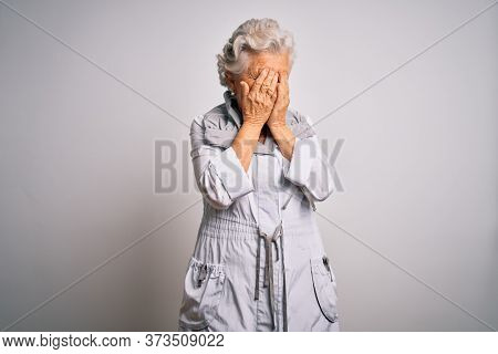 Senior beautiful grey-haired woman wearing casual jacket standing over white background with sad expression covering face with hands while crying. Depression concept.