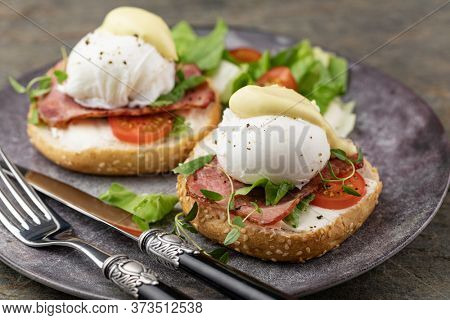 Delicious breakfast with eggs Benedict and salad